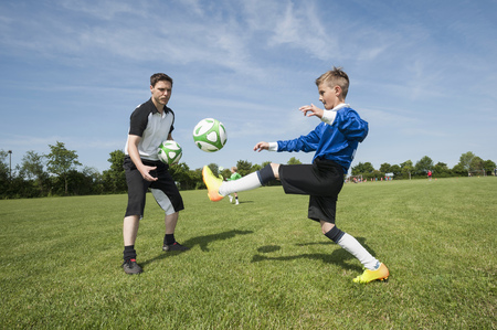 Soccer trainer teaching young player helping LANG_EVOIMAGES