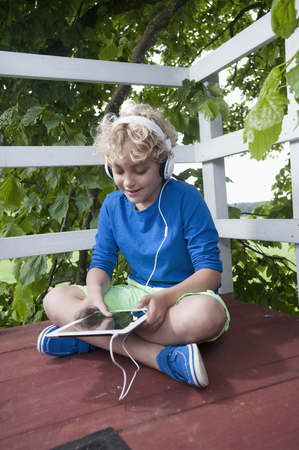 lust for life: Boy sitting tree-house tablet computer headphones