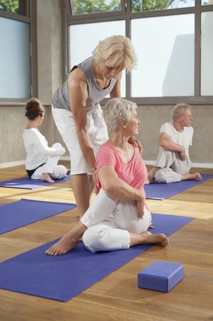 plainness: Man Yoga trainer teaching group exercises LANG_EVOIMAGES