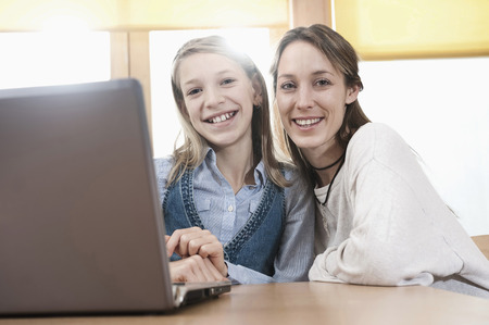 learning computer: Portrait of schoolgirl and female childcare assistant with laptop LANG_EVOIMAGES