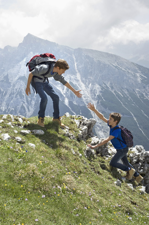 perilous: Teenage boys helping friend climbing in mountains