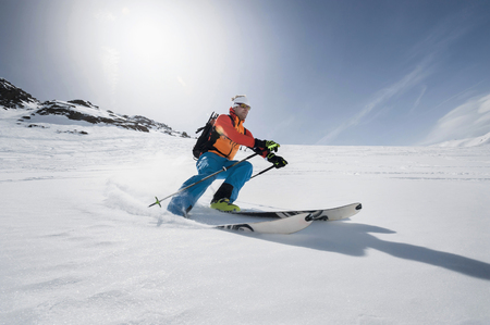 lust for life: Man skiing downhill powder snow Alps sunshine