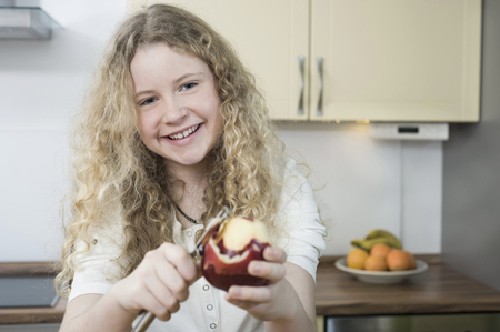 parer: Girl in kitchen peeling apple