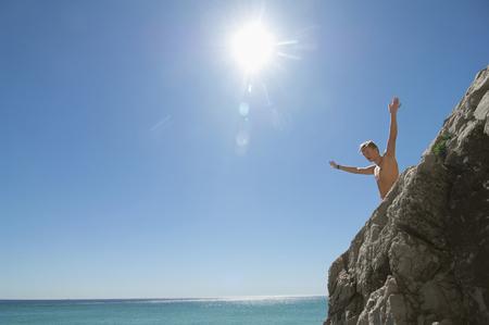 Standing preparing jump cliff diving ocean boy