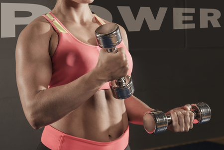Detail close up muscular woman weight training LANG_EVOIMAGES