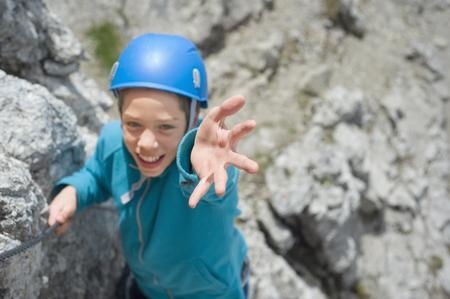 Teenager climbing Alps mountains reaching helping