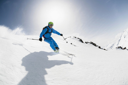 perilous: Man skier skiing downhill steep slope sunshine LANG_EVOIMAGES