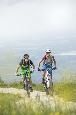 Mountain bikers cycling uphill in nature, Kampenwand, Bavaria, Germany LANG_EVOIMAGES