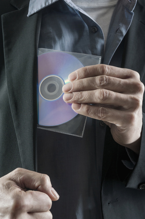software portability: Businessman stealing compact disk, Bavaria, Germany LANG_EVOIMAGES