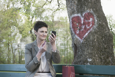self conceit: Mature woman applying lipstick for her dating in park, Bavaria, Germany