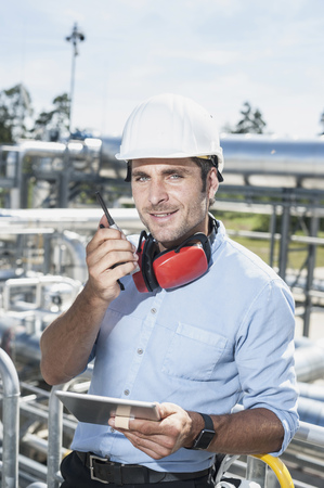 Male engineer talking with walkie-talkie at geothermal power station, Bavaria, Germany