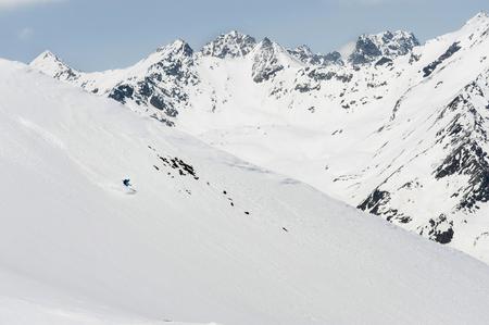 lust for life: Man skiing downhill steep ski slope Alps