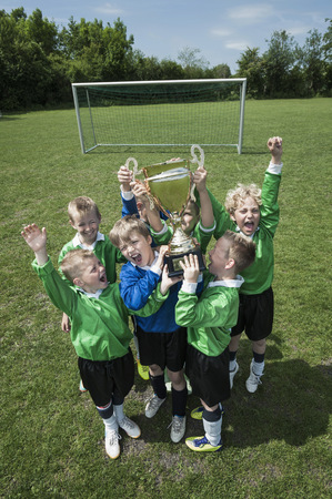 Young boys soccer team holding trophy