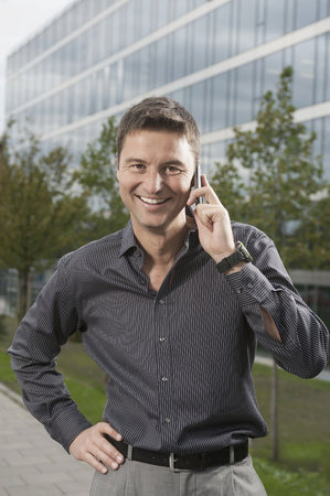 Smart businessman speak a cell phone standing in front of an office building, Bavaria, Germany LANG_EVOIMAGES