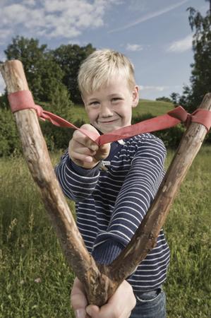 lust for life: Young boy holding wooden slingshot smiling LANG_EVOIMAGES