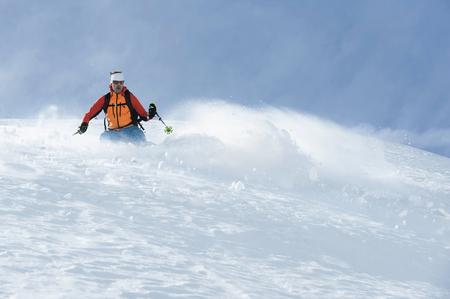 lust for life: Man skiing downhill deep powder snow Alps