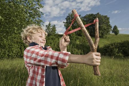 lust for life: Boy holding handmade wooden slingshot