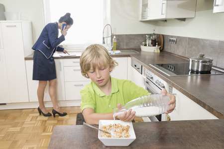 primary product: Boy pouring milk in muesli while mother has business call in kitchen, Bavaria, Germany LANG_EVOIMAGES