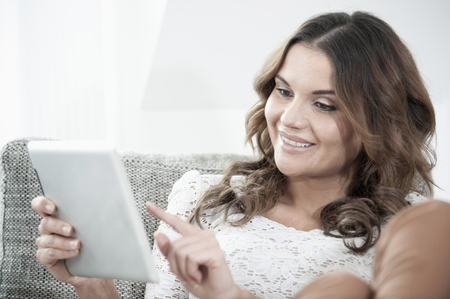 Portrait of smiling young woman with digital tablet sitting on couch at home
