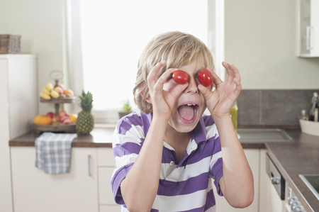 about age: Playful boy making face with tomatoes, Bavaria, Germany