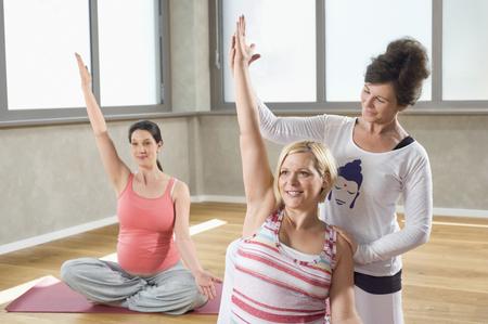 plainness: Female Yoga coach teaching pregnant women
