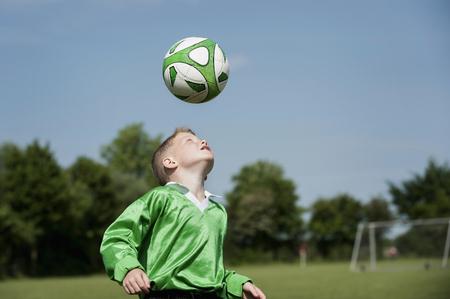Young boy soccer practice football header ball