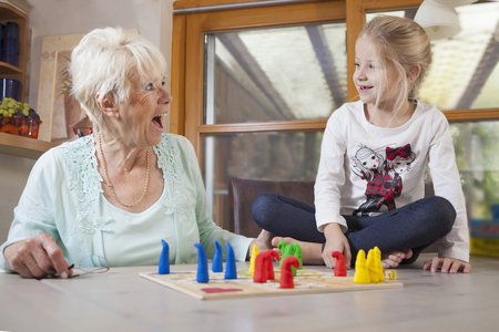 about age: Girl playing board game with her grandmother, Bavaria, Germany LANG_EVOIMAGES