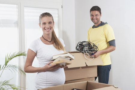 two people fertility: Pregnant woman packing with her husband while moving to new apartment, Bavaria, Germany