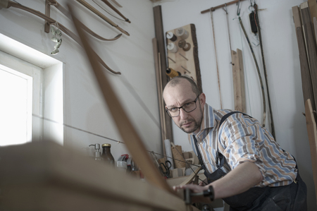 hairline: Male bow maker making bow in workshop, Bavaria, Germany