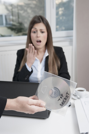 freaked: Hand holding CD, young horrified business woman sitting in the background