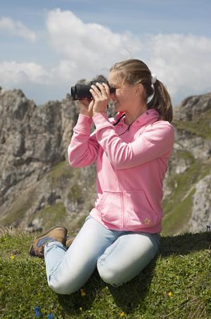 Teenage girl holding binoculars mountains viewing LANG_EVOIMAGES