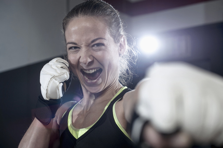 Portrait of a sportswoman in boxing pose in the gym, Bavaria, Germany LANG_EVOIMAGES