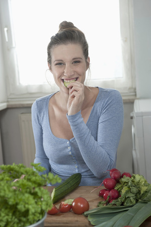 tied in: Woman eating salad kitchen preparing meal healthy LANG_EVOIMAGES