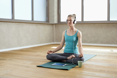 plainness: Woman in fitness studio meditating tablet computer