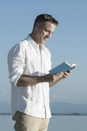 german ethnicity: Mature man reading book and smiling at lakeside, Bavaria, Germany