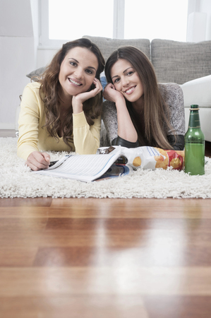 Two smiling female friends lying side by side on carpet at home LANG_EVOIMAGES