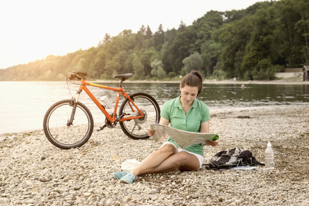 Mature woman with electric bike by lake looking at road map, Bavaria, Germany LANG_EVOIMAGES