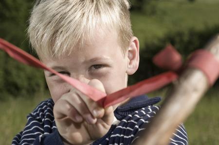 lust for life: Close up blond boy holding slingshot