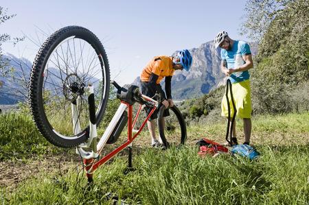 Mountainbikers repairing flat type on E-bike