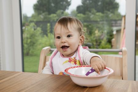Smiling happy baby girl portrait table bowl LANG_EVOIMAGES