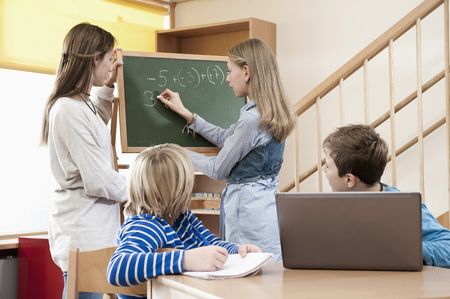 figuring: Female childcare assistant helping children by doing homework