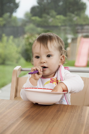 Baby girl portrait table bowl eating happy LANG_EVOIMAGES