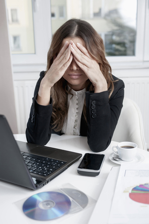 overstress: Young over-burdened businesswoman at her workplace
