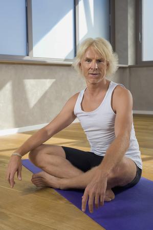 looking away from camera: Portrait senior man in Yoga studio floor