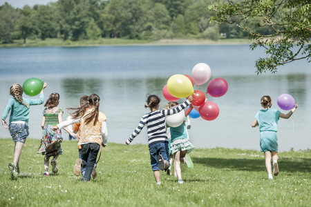 multi age: Rear view of children running in park with balloons, Munich, Bavaria, Germany