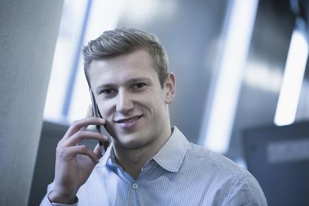 Portrait of young man talking on mobile phone in locker room, Freiburg im Breisgau, Baden-Württemberg, Germany