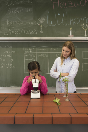 german ethnicity: School girl with teacher looking through a microscope, Fürstenfeldbruck, Bavaria, Germany