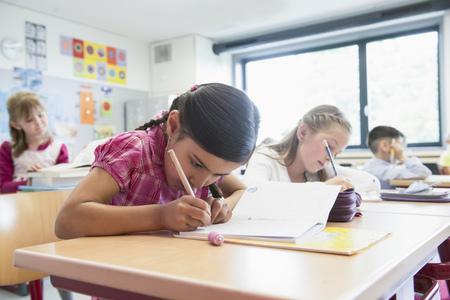 german ethnicity: School students writing notebooks in classroom, Munich, Bavaria, Germany