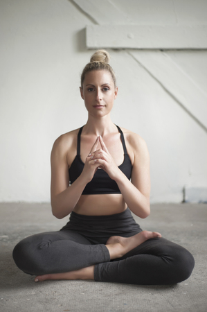 Mid adult woman meditating lotus pose in yoga studio, Munich, Bavaria, Germany