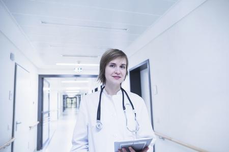 freiburg: Young female doctor holding clipboard in hospital corridor, Freiburg im breisgau, Baden-Württemberg, Germany